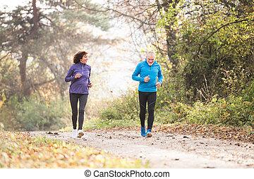 Beautiful senior couple running outside in sunny autumn...