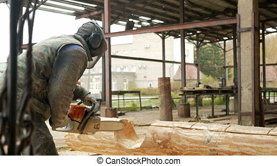 Man cuts wood chainsaw for future home. Protective face mask...