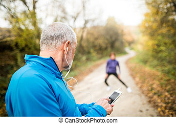 Senior runners in nature, stretching. Man with smartphone...