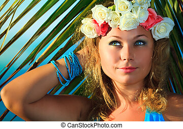 Woman in flower diadem on the beach