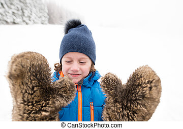 Cute boy wearing big furry gloves outside in winter nature -...