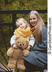 The mother, her daughter and toy Teddy bear posing  walking in autumn park, close up