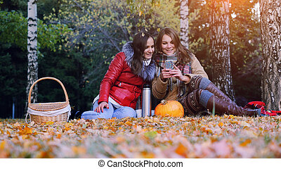 Girls using smartphone on a picnic in autumn park sitting  the fallen leaves near the pumpkin at halloween time.