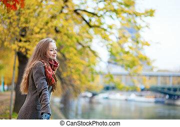 Beautiful young girl enjoying autumn day in Paris