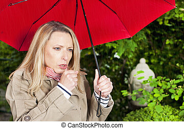 Woman with umbrella coughing outdoor
