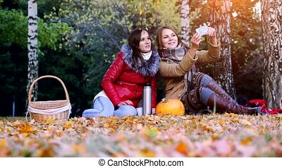 Beautiful brunette girls making selfie on a picnic in autumn...