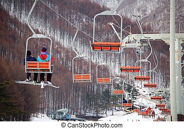 Snow Resort - gondola - A couple takes ride of gondola at a...