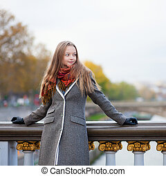 Beautiful young lady in Paris on a bridge