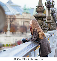 Romantic young woman with beautiful long hair on a bridge in Paris