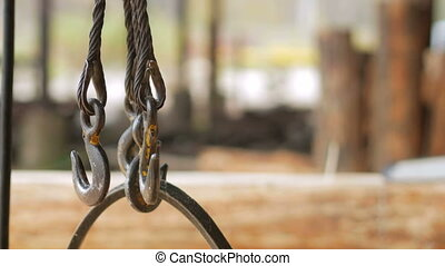 Hook of Overhead Winch Crane close-up. Builder sawing wood...