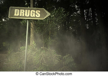 old signboard with text drugs near the sinister forest -...