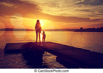 Silhouettes of Mother and Her Son by the Lake - Silhouettes...