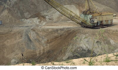 The excavator works in a quarry. It removes the top layer of...