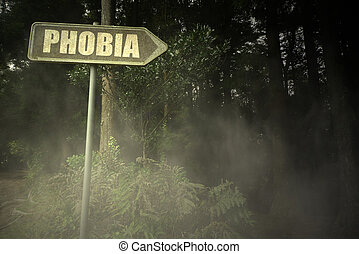 old signboard with text phobia near the sinister forest -...