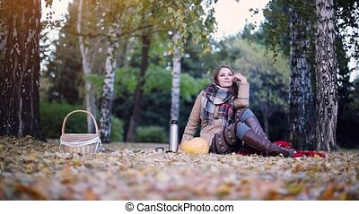Young woman uses smartphone on a picnic in autumn park sitting the fallen leaves near the pumpkin at halloween time. 1920x1080