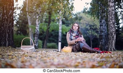 Thoughtful woman sitting on picnic next to the pumpkin in...
