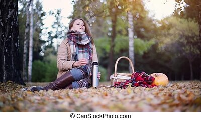 Young woman sitting on picnic next to the pumpkin drinking...