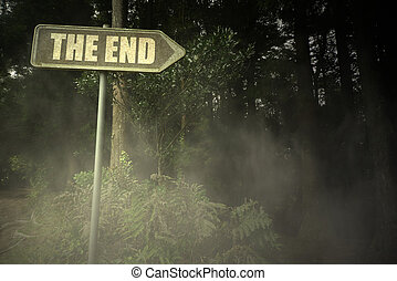 old signboard with text the end near the sinister forest -...