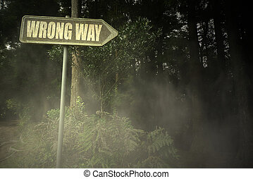 old signboard with text wrong way near the sinister forest -...