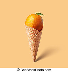 Waffle cornet with orange isolated on yellow