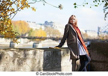 Parisian girl on the embankment on a fall day