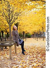 Pretty young girl enjoying a beautiful autumn day in Paris