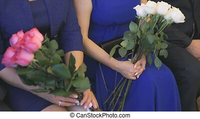 Two women hold the bouquets of roses - Two women sitting and...