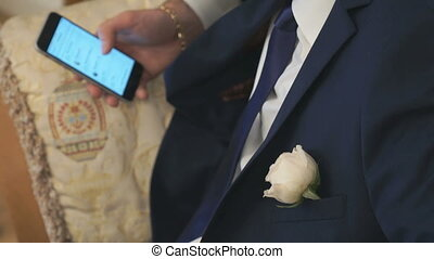 The groom sitting on chair holds the mobile phone - The...