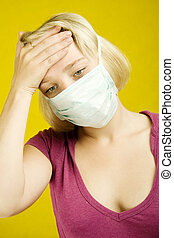 Flu - Young woman on a yellow background in a protective...