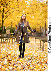Girl playing with autumn leaves in park