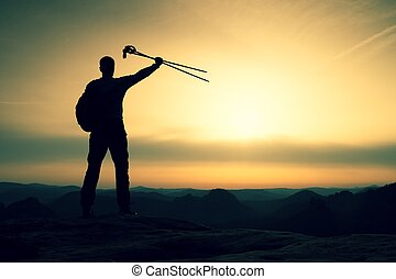 Silhouette with poles in hand above head. Sunny daybreak i -...