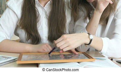 Two schoolgirls looking photo frame with a picture - Two...