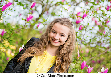 Laughing girl with blooming magnolia