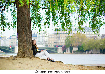 Girl reading a book under the tree