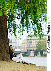 Girl reading under a tree in Paris