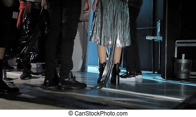 Models entering the catwalk from backstage. Legs view.