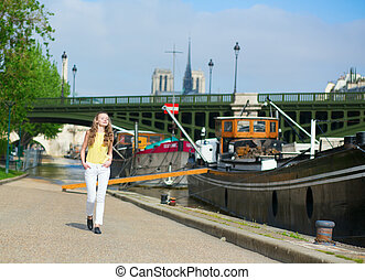Girl walking near boats on the Seine
