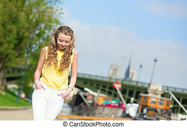 Girl walking on a Parisian embankment