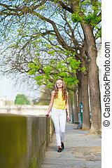 Girl walking by the Seine in Paris