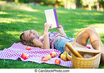 Beautiful young girl reading a book in park