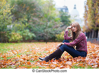 Thoughtful girl sitting on the ground at fall - Thoughtful...