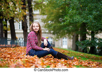 Thoughtful girl sitting on the ground at fall.