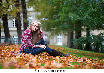Thoughtful girl sitting on the ground at fall