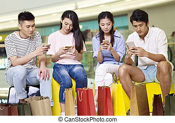 young asian people playing with mobile phones - a group of...