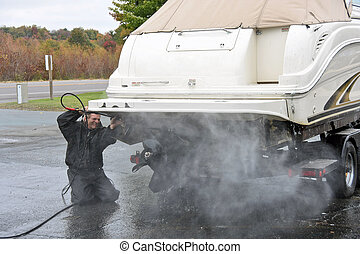 man cleaning power boat