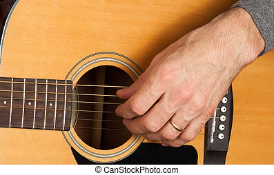Man's hand playing the guitar. The concept of discipleship....