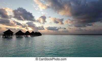 Maldives. houses on piles on water at the time sunset