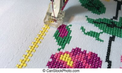 Embroidery flower design cross on white cloth, close-up