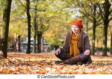 Young beautiful girl sitting on the ground at fall