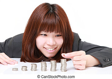 Businesswoman put coins to stack of coins - concept shot of...